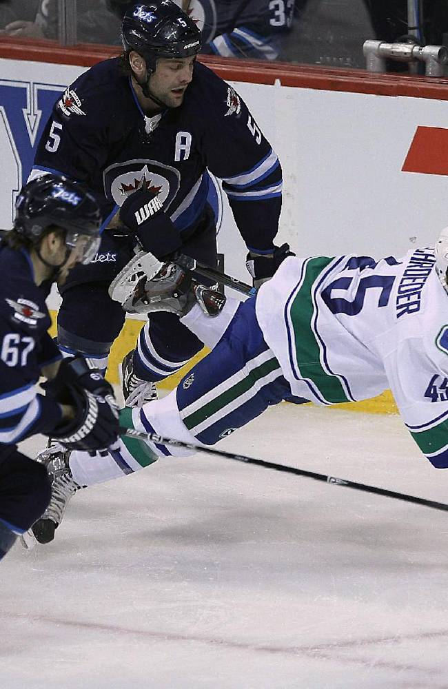 Vancouver Canucks' Jordan Schroeder (45) gets tripped by Winnipeg Jets' Michael Frolik (67) and Mark Stuart (5) during the first period of an NHL hockey game Wednesday, March 12, 2014, in Winnipeg, Manitoba