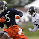 Chicago Bears wide receiver Brandon Marshall (15), left, runs with a ball past cornerback Tim Jennings (26) during team's NFL football training camp at Olivet Nazarene University on Friday, July 25, 2014., in Bourbonnais, Ill The Associated Press