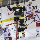 Boston Bruins center Gregory Campbell falls behind the goal as his teammates celebrate after his goal against the New York Rangers during the second period in Game 5 of the Eastern Conference semifinals in the NHL hockey Stanley Cup playoffs in Boston, Saturday, May 25, 2013. (AP Photo/Charles Krupa)