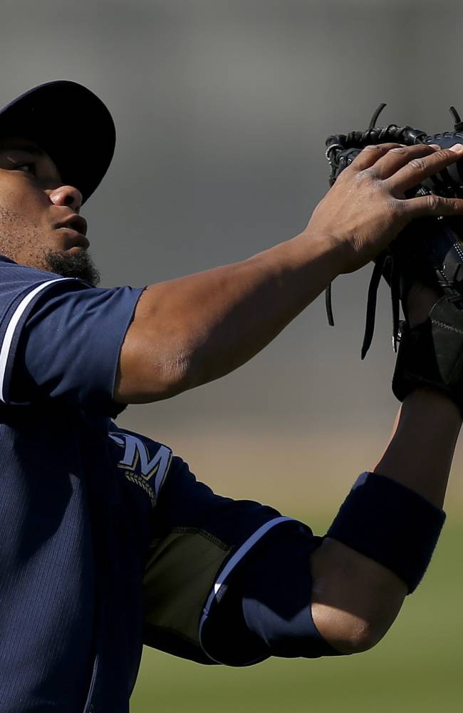 Milwaukee Brewers' Martin Maldonado misplays a high pop fly during Brewers spring training baseball practice, Thursday, Feb. 20, 2014, in Phoenix