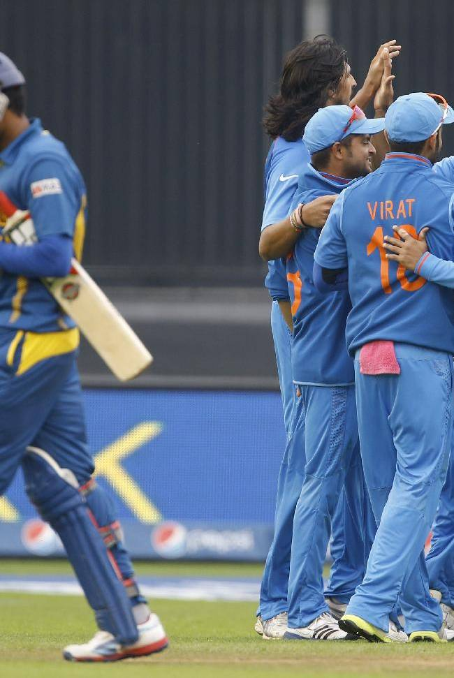 India's players celebrate the wicket of Sri Lanka's Lahiru Thirimanna, left, during an ICC Champions Trophy semifinal between India and Sri Lanka at the Cardiff Wales Stadium in Cardiff, Thursday, June 20, 2013