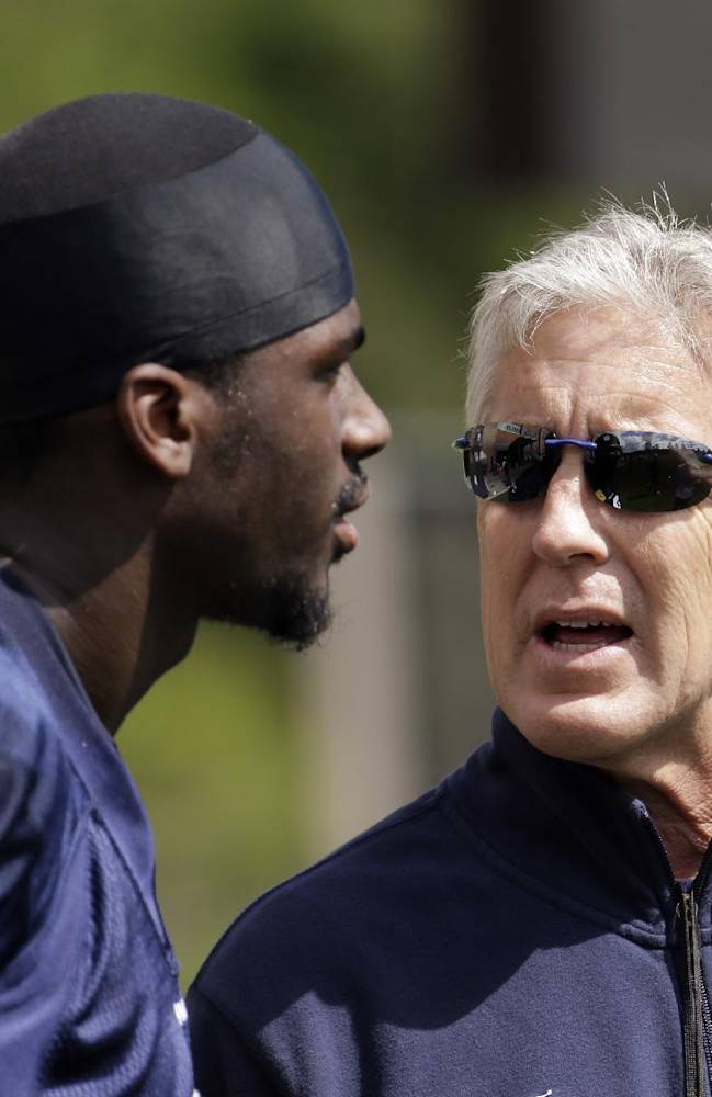 Seattle Seahawks coach Pete Carroll, right, talks with Kevin Norwood after NFL football rookie minicamp Saturday, May 17, 2014, in Renton, Wash