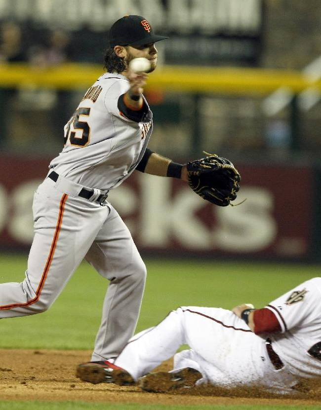 San Francisco Giants shortstop Brandon Crawford (35) turns the double play while avoiding Arizona Diamondbacks Miguel Montero (26) in the first inning during a baseball game, Tuesday, April 1, 2014, in Phoenix