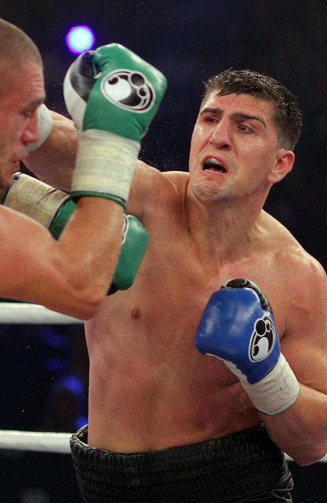 In  this picture taken Saturday Aug. 30, 2014 German boxer Marco  Huck right,  hits  Italian challenger Mirko Larghetti during their WBO cruiserweight title bout in Halle, western Germany.  German defending cruiserweight champion  Marco Huck defeated Mirko Larghetti of Italy by unanimous decision Saturday to retain his WBO belt for the record-equaling 13th time