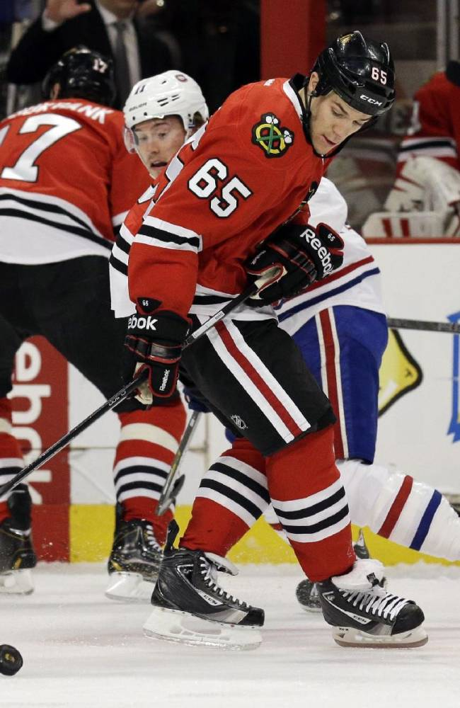Chicago Blackhawks' Andrew Shaw (65) battles for the puck against Montreal Canadiens' Brendan Gallagher (11) during the first period of an NHL hockey game in Chicago, Wednesday, April 9, 2014