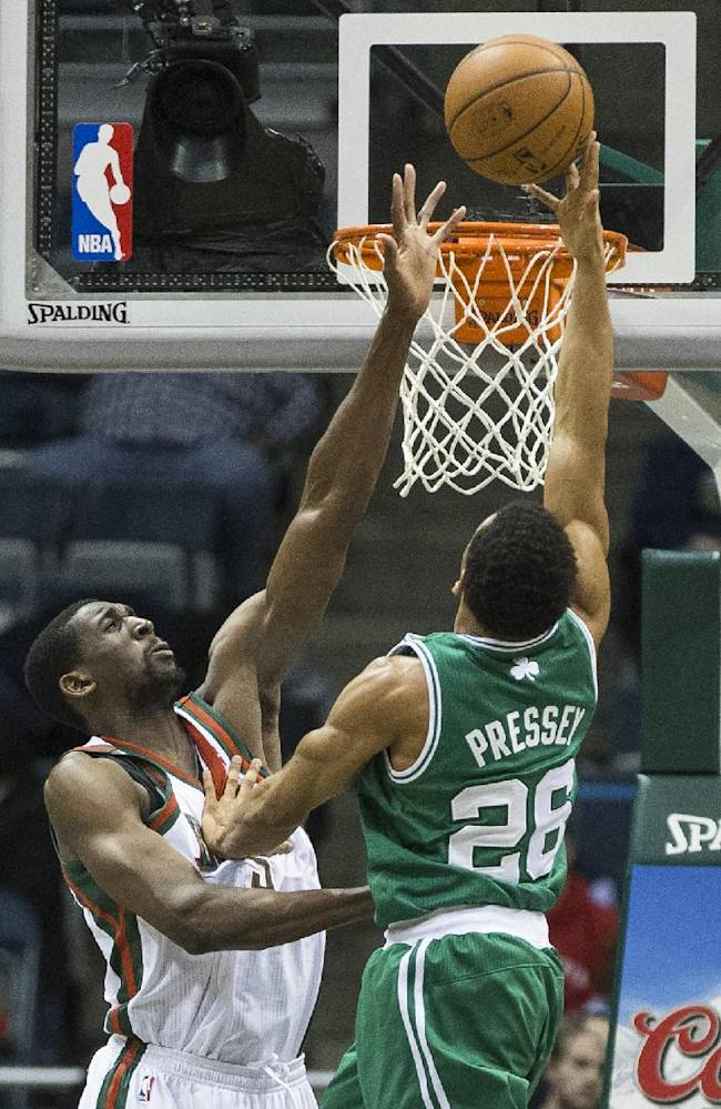 Milwaukee Bucks' Ekpe Udoh attempts to block the shot of Boston Celtics' Phil Pressey during the second half of an NBA basketball game, Monday, Feb. 10, 2014, in Milwaukee