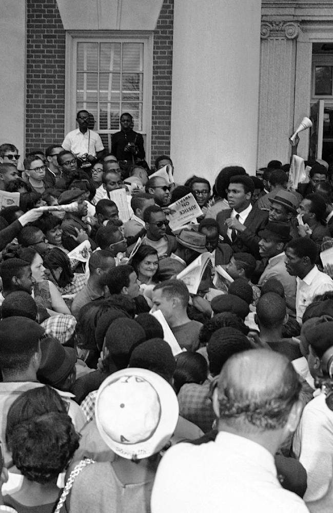 In this April 22, 1967 file photo, heavyweight boxing champion Muhammad Ali, center right, rear, wearing a white shirt and tie, holds a paper as he addresses a rally at Howard University in Washington. Barely past the opening credits of a new documentary about Ali, and we get a glimpse of how many Americans felt about him during a tumultuous time in the country's history.  For those who didn't live in the time and are only faintly aware of the tale, it is a remarkable one