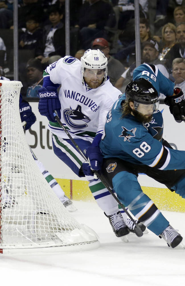 San Jose Sharks' Brent Burns (88) is chased by Vancouver Canucks' Ryan Stanton (18) as goalie Roberto Luongo, left, watches during the first period of an NHL hockey game Thursday, Oct. 3, 2013, in San Jose, Calif