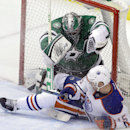 Edmonton Oilers defenseman Nick Schultz (15) slides into Dallas Stars goalie Kari Lehtonen during the first period of an NHL hockey game Sunday, Dec. 1, 2013, in Dallas. A penalty was called on the play The Associated Press