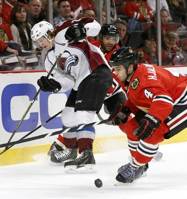 Colorado Avalanche center Nathan MacKinnon, left, loses the puck as Chicago Blackhawks defenseman Johnny Oduya, center, and defenseman Niklas Hjalmarsson (4) defend during the first period of an NHL hockey game Tuesday, March 4, 2014, in Chicago