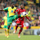Norwich City's Alex Tettey, left, is challenged by West Bromwich Albion's Stephane Sessegnon during the English Premier League soccer match at Carrow Road, Norwich, England, Saturday April 5, 2014