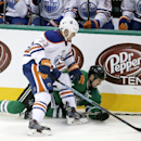 Dallas Stars' Jamie Benn (14) falls to the ice after a collision with Edmonton Oilers' Matt Hendricks (23) as the two chased a loose puck in the third period of an NHL hockey game, Tuesday, Nov. 25, 2014, in Dallas. The Stars won 3-2 The Associated Press