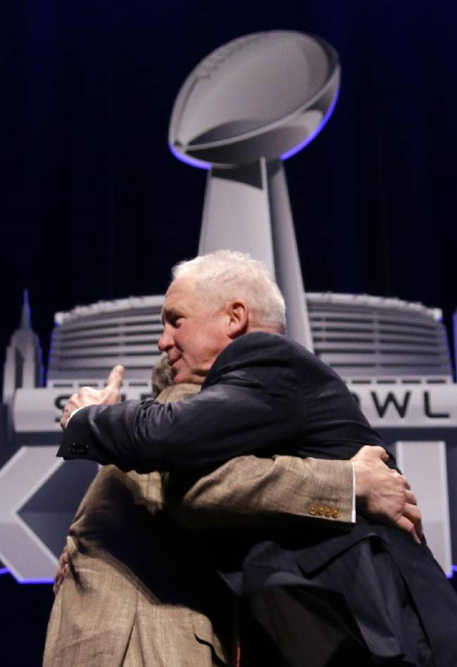 Seattle Seahawks head coach Pete Carroll and Denver Broncos head coach John Fox, right, hug each other after speaking to the media at a news conference Friday, Jan. 31, 2014, in New York. The Seahawks and the Broncos are scheduled to play in the NFL Super Bowl XLVIII football game on Sunday, Feb. 2, at MetLife Stadium in East Rutherford, N.J