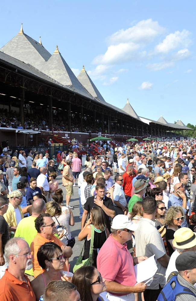 Fans watch the racing action on opening day of the horse racing season at Saratoga Race Course in Saratoga Springs, N.Y., Friday, July 18, 2014