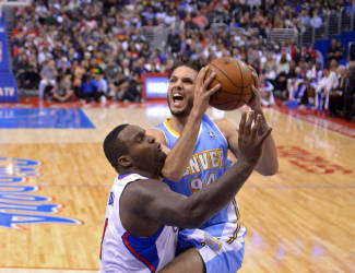 Denver Nuggets guard Evan Fournier, right, goes up for a shot as Los Angeles Clippers forward Glen Davis defends during the first half of an NBA basketball game, Tuesday, April 15, 2014, in Los Angeles. (AP Photo/Mark J. Terrill)