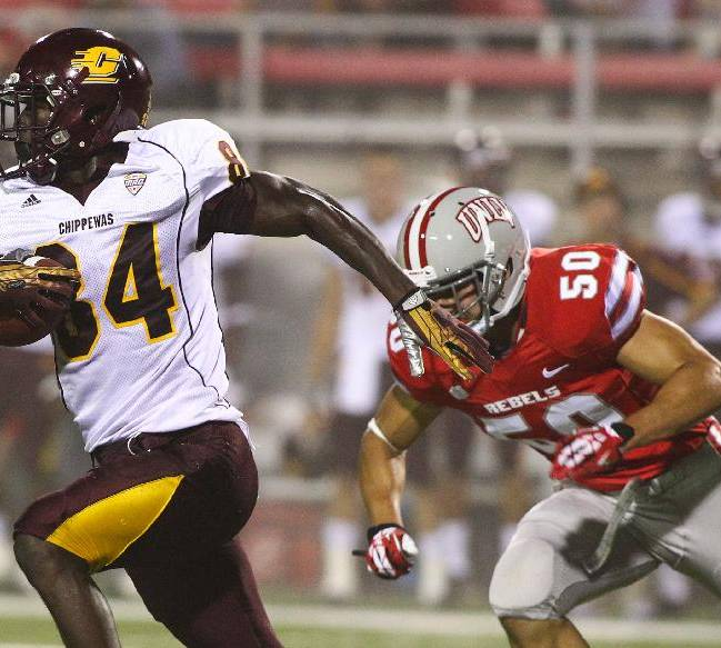 Central Michigan's Titus Davis (84) runs past UNLV's Trent Langham (50) during the first half of an NCAA college football game at Sam Boyd Stadium in Las Vegas on Saturday, Sept. 14, 2013