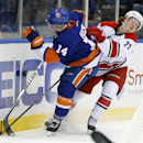 Carolina Hurricanes left wing Brock McGinn (21) battles for the puck with New York Islanders defenseman Thomas Hickey (14) in the first period of a preseason NHL hockey game Wednesday, Sept. 24, 2014, in Uniondale, N.Y. The Associated Press