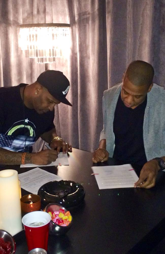 In this photo provided by Roc Nation Sports, New York Yankees pitcher CC Sabathia, left, signs papers with Jay-Z as Sabathia signs on with Jay-Z's sports agency, Roc Nation Sports, Thursday, Jan. 16, 2014, in New York. Sabathia will join former teammate Robinson Cano in Roc Nation Sport's emerging client base