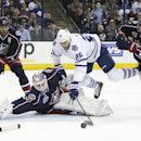 Toronto Maple Leafs' Daniel Winnik (26) dives over Columbus Blue Jackets goalie Curtis McElhinney (30) as Blue Jackets' Fedor Tyutin, left, of Russia, and Jack Johnson (7) close in during the first period of an NHL hockey game, Friday, Oct. 31, 2014, in C