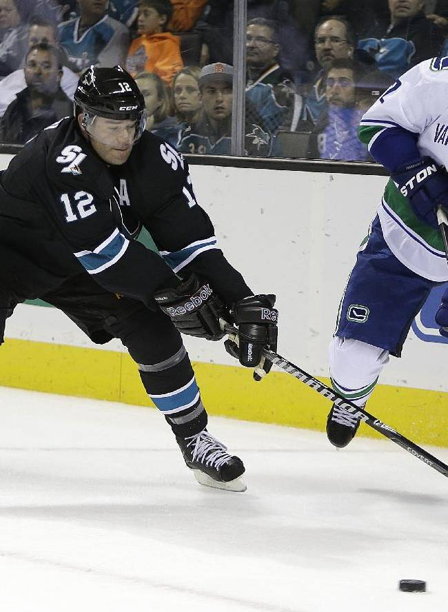 Vancouver Canucks' Dan Hamhuis, right, and San Jose Sharks' Patrick Marleau (12) fight for the puck during the first period of an NHL hockey game on Thursday, Nov. 7, 2013, in San Jose, Calif