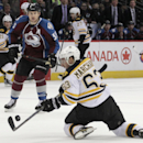 Boston Bruins left wing Brad Marchand (63) swats at the puck as Colorado Avalanche left wing Cody McLeod (55) watches the second period of an NHL hockey game in Denver on Friday, March 21, 2014 The Associated Press