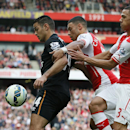 Hull City's Hatem Ben Arfa, left, holds off Arsenal's Alex Oxlade-Chamberlain, center, and Kieran Gibbs during the English Premier League soccer match between Arsenal and Hull City at the Emirates stadium in London Saturday, Oct.18, 2014