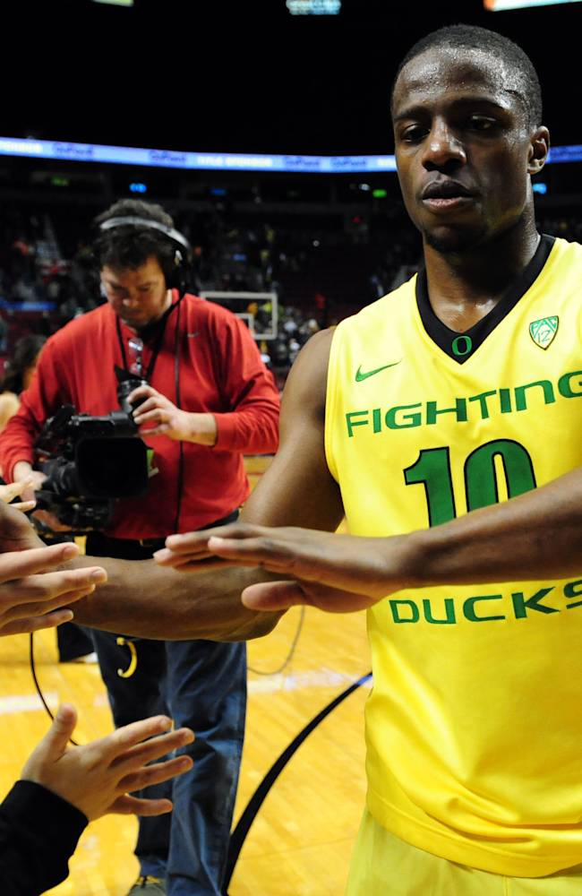 Oregon guard Johnathan Loyd (10) greets some fans as he runs off the court after an NCAA college basketball game against the Illinois in Portland, Or., Saturday, Dec. 14, 2013. Oregon won the game 71-64