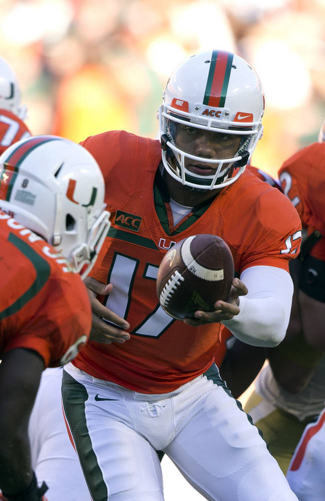 Miami quarterback Stephen Johnson (17) hands the ball to Duke Johnson (8) during the second half of an NCAA college football game against Georgia Tech in Miami Gardens, Fla., Saturday, Oct. 5, 2013. Miami won 45-30