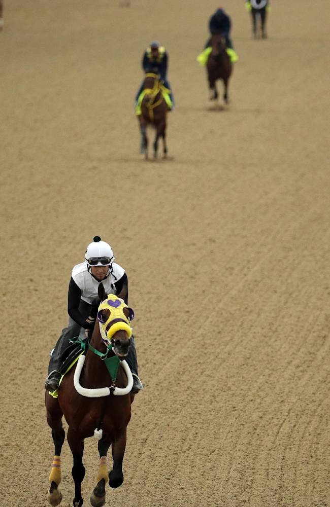 Exercise rider Benito Alvarado takes Kentucky Derby hopeful Uncle Sigh for a morning workout at Churchill Downs Wednesday, April 30, 2014, in Louisville, Ky