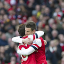 Arsenal's Laurent Koscielny, right, celebrates with teammate Santi Cazorla after scoring against Sunderland, during their English Premier League soccer match, at Emirates Stadium, in London, Saturday, Feb. 22, 2014