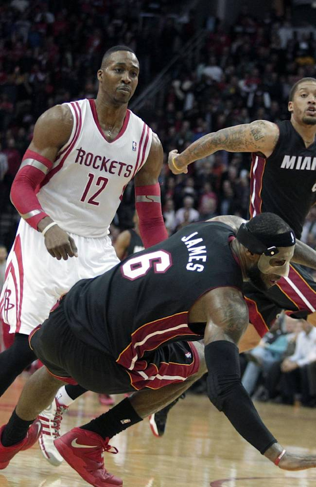 Miami Heat forward LeBron James (6) falls to the ground after colliding with Houston Rockets center Dwight Howard (12) during the fourth quarter of an NBA basketball game, Tuesday, March, 4, 2014, in Houston. The Rockets defeated the Heat 106-103