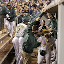 Oakland Athletics' Derek Norris, lower right, and Josh Reddick run through a tunnel formed by their teammates in the dugout after Norris hit a two-run home run against the Seattle Mariners in the seventh inning of a baseball game, Friday, Sept. 27, 2013, in Seattle. (AP Photo/Ted S. Warren)