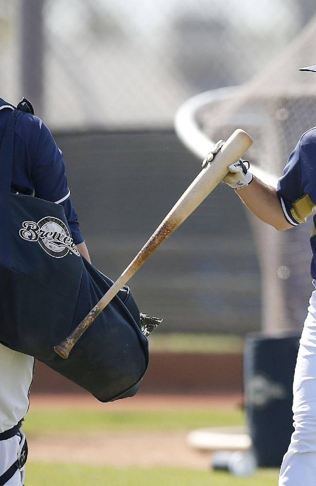 Milwaukee Brewers' Adam Weisenburger, right, hits his bat on Jonathan Lucroy's bag of catching gear after finishing his batting practice during baseball spring training Wednesday, Feb. 26, 2014, in Phoenix