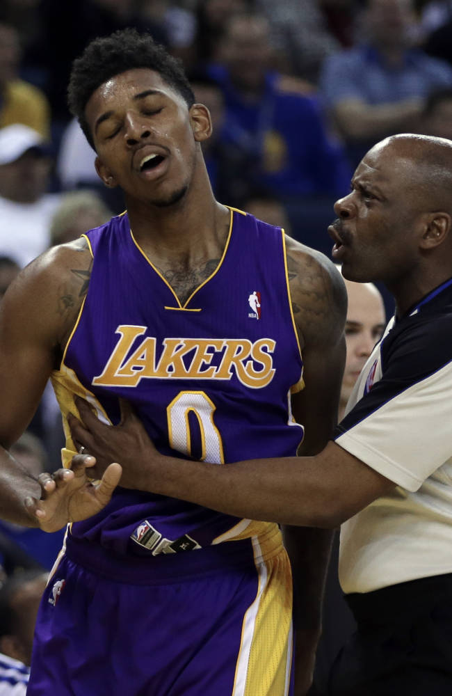Los Angeles Lakers' Nick Young, left is restrained by referee Derek Richardson during the second half of an NBA basketball game against the Golden State Warriors Saturday, Dec. 21, 2013, in Oakland, Calif