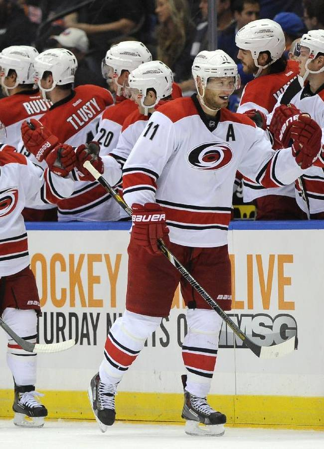 Carolina Hurricanes' Jordan Staal (11) and Nathan Gerbe (14) celebrate Staal's goal against the New York Islanders with teammates in the second period of an NHL hockey game Saturday, Oct. 19, 2013, in Uniondale, N.Y