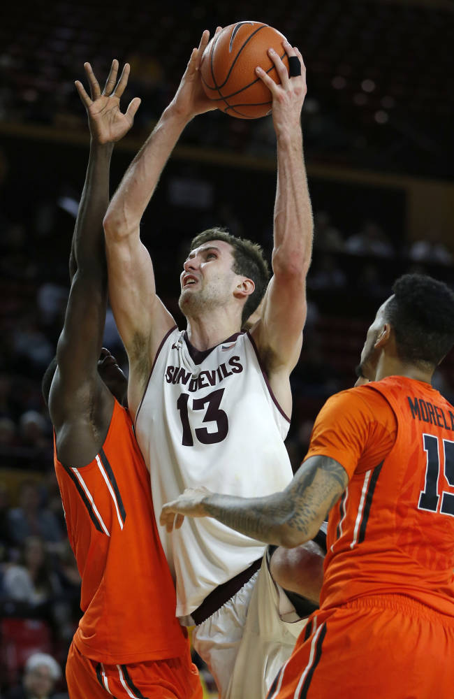 Arizona State's Jordan Bachynski (13) shoots over Oregon State's Eric Moreland (15) and Daniel Gomis during the second half of an NCAA college basketball game, Thursday, Feb. 6, 2014, in Tempe, Ariz