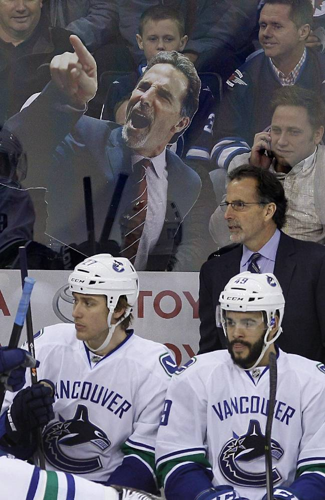 Winnipeg Jets fans taunt Vancouver Canucks coach John Tortorella during the first period of an NHL hockey game Wednesday, March 12, 2014, in Winnipeg, Manitoba