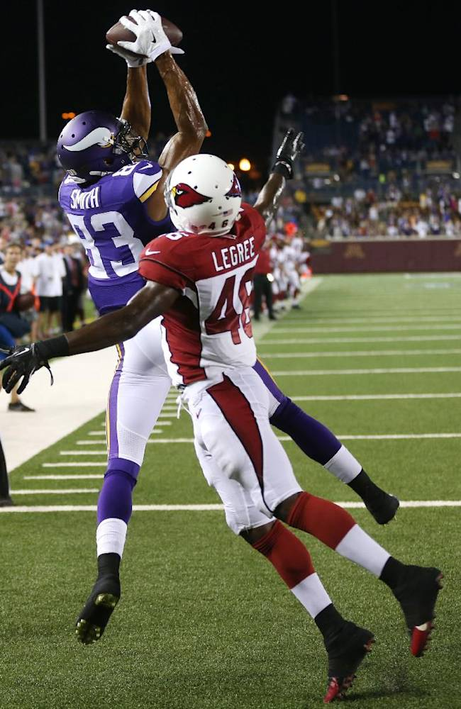 Minnesota Vikings wide receiver Rodney Smith, left, catches a 2-yard touchdown pass over Arizona Cardinals defensive back Jimmy Legree during the second half of an NFL preseason football game, Saturday, Aug. 16, 2014, in Minneapolis. The Vikings won 30-28