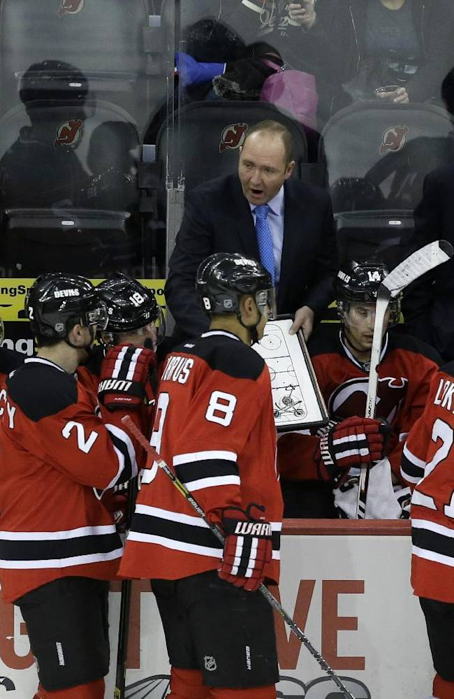 New Jersey Devils head coach Peter DeBoer draws a play on the bench late in the third period of an NHL hockey game against the San Jose Sharks, Sunday, March. 2, 2014, in Newark, N.J. The Sharks won 4-2