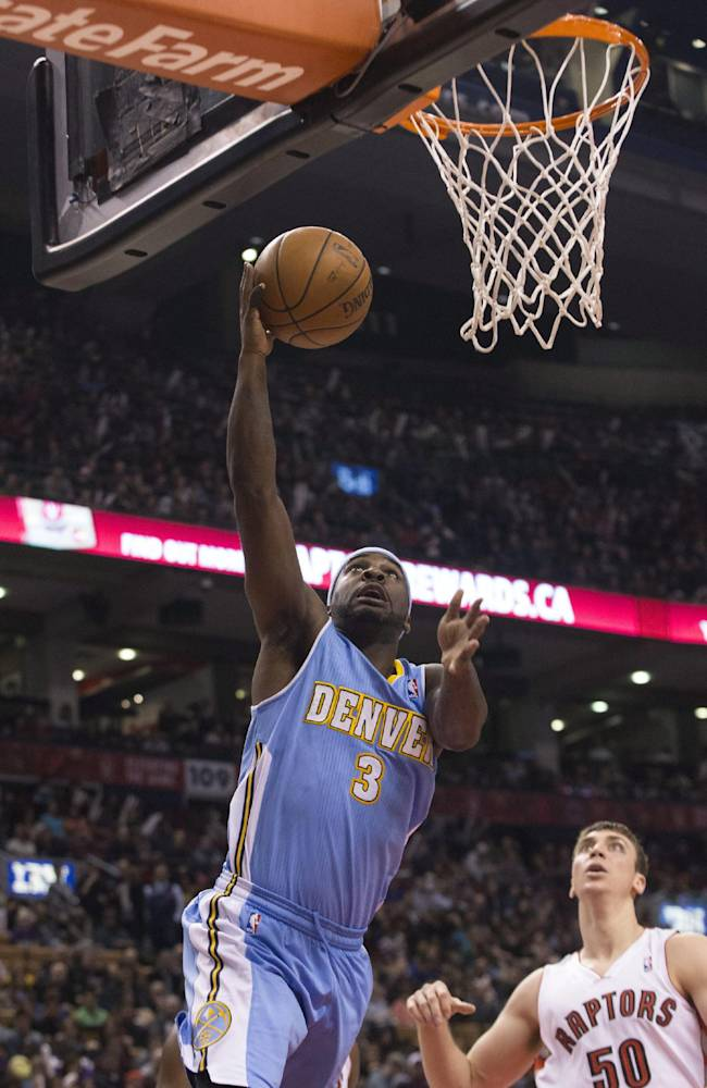 Denver Nuggets' Ty Lawson, left, goes up for a basket as Toronto Raptors' Tyler Hansbrough looks on during first half of an NBA basketball game on Sunday, Dec. 1, 2013, in Toronto