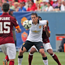 Manchester United's Javier Hernandez, center, tries to evade AS Roma's Ashley Cole during an exhibition soccer match at Mile High Stadium in Denver, Saturday, July 26, 2014. Manchester United won 3-2