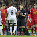 Referee Mike Jones reasons with Swansea City's Ashley Williams, centre left as Liverpool's Jordan Henderson, right, looks on during their English Premier League soccer match at Anfield Stadium, Liverpool, England, Sunday Feb. 23, 2014