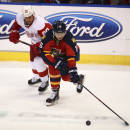 Florida Panthers' Aleksander Barkov (16) steals the puck from Detroit Red Wings' Stephen Weiss (90) during the first period of an NHL hockey game in Sunrise, Fla., Tuesday, Jan. 27, 2015. (AP Photo/J Pat Carter)