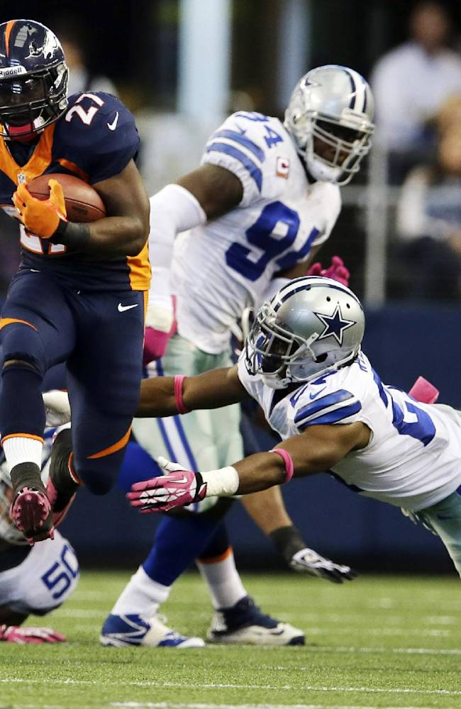 Denver Broncos' Knowshon Moreno (27) eludes Dallas Cowboy's J.J. Wilcox, right, during the second quarter of an NFL football game Sunday, Oct. 6, 2013, in Arlington, Texas
