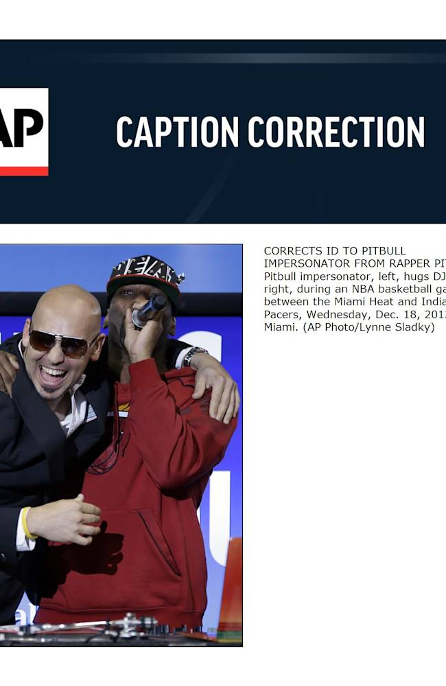 CORRECTS ID TO PITBULL IMPERSONATOR FROM RAPPER PITBULL - Pitbull impersonator, left, hugs DJ Irie, right, during an NBA basketball game between the Miami Heat and Indiana Pacers, Wednesday, Dec. 18, 2013, in Miami