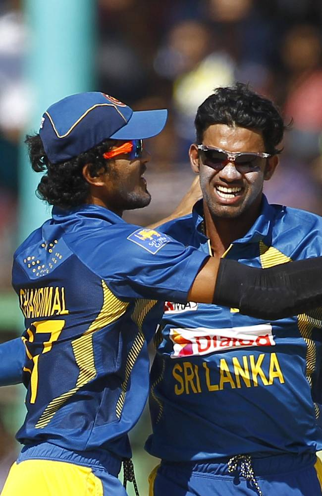 Sri Lanka's Sachithra Senanayake, right, celebrates with his teammate Dinesh Chandimal dismissal of India's Rohit Sharma during the Asia Cup one-day international cricket tournament,  in Fatullah, near Dhaka, Bangladesh, Friday, Feb. 28, 2014