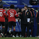 Manchester United's Marouane Fellaini, center, celebrates scoring his side's first goal with manager Louis van Gaal, second right, and Wayne Rooney during the English Premier League soccer match between QPR and Manchester United at Loftus Road stadium in
