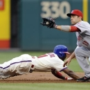 Philadelphia Phillies' Jimmy Rollins, left, dives back to first base and beats the tag from Cincinnati Reds' Joey Votto (19) in the third inning of a baseball game on Saturday, May 18, 2013, in Philadelphia. (AP Photo/Michael Perez)