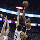 Brooklyn Nets guard Joe Johnson (7) attempts a shot while defended by Utah Jazz center Enes Kanter (0), of Turkey, and guard Trey Burke (3) during the first half of an NBA basketball game Wednesday, Feb. 19, 2014, in Salt Lake City The Associated Press