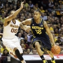 Michigan guard Trey Burke, right, drives against Minnesota guard Julian Welch (00) during the first half of an NCAA college basketball game, Thursday, Jan. 17, 2013, in Minneapolis. Burke wore the No. 12 because of an issue with his No. 3 jersey. (AP Photo/Paul Battaglia)
